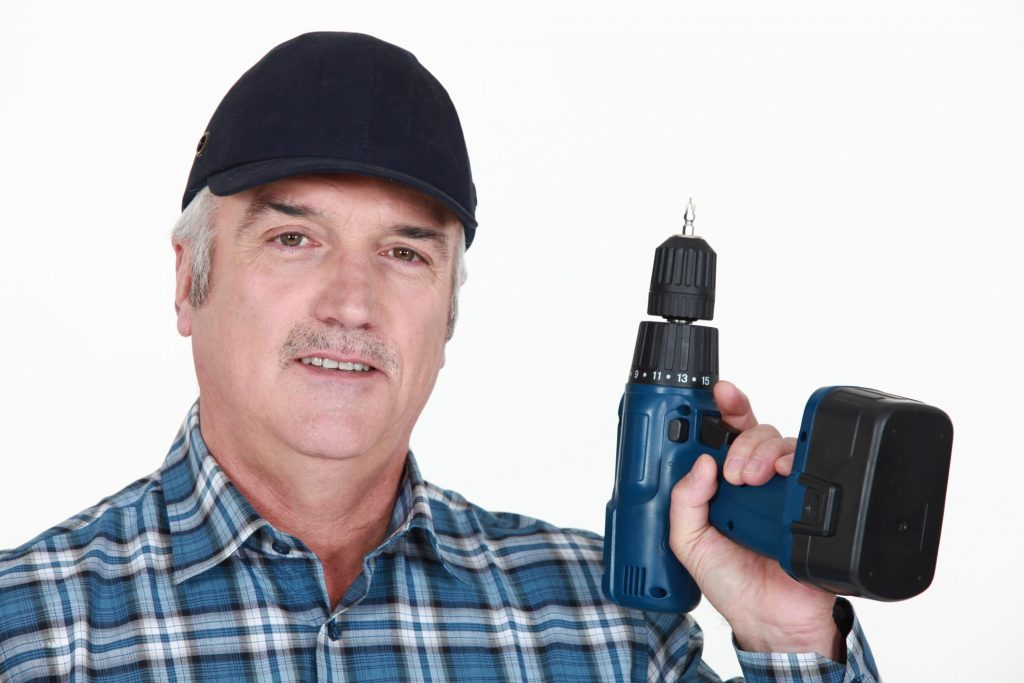 man in stripe holding power drill