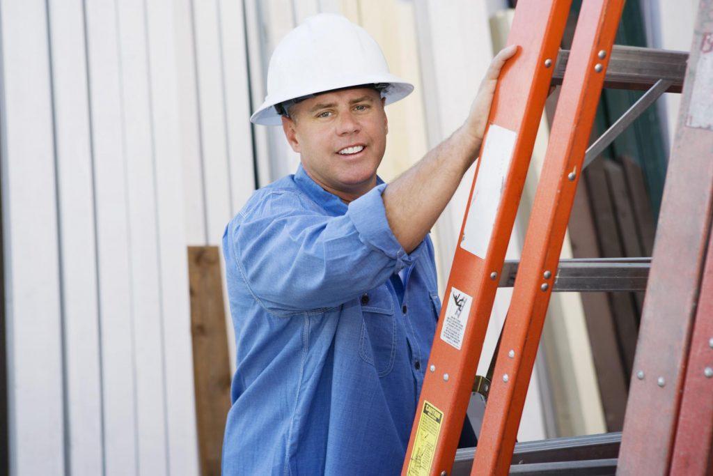 man in white hard hat using ladder