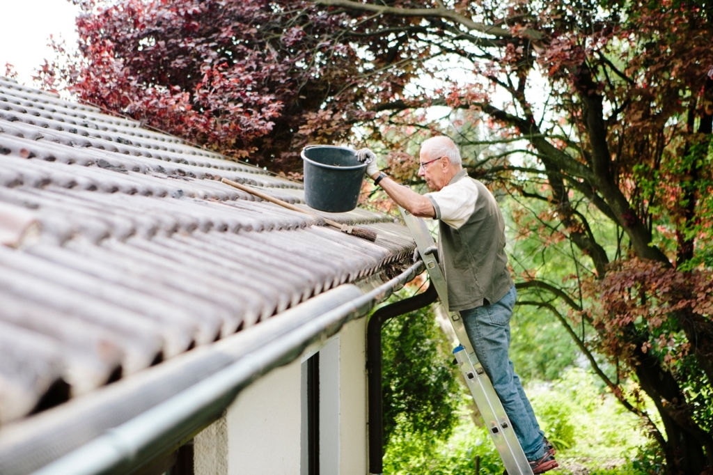 photo of a man cleaning his gutter