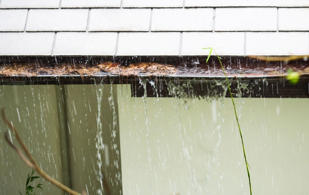 close up view on clogged rain gutter in the rain home guttering gutters